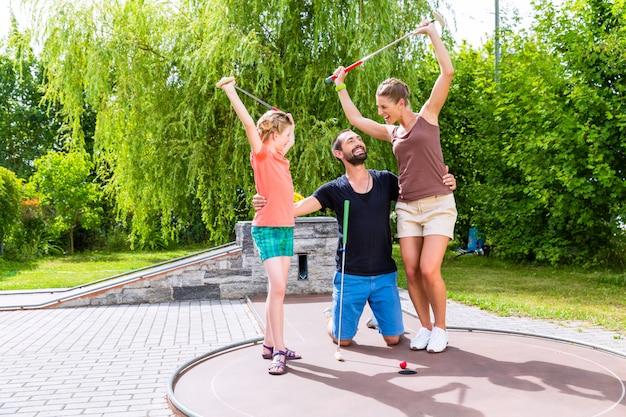 Famille jouant au golf miniature en plein air