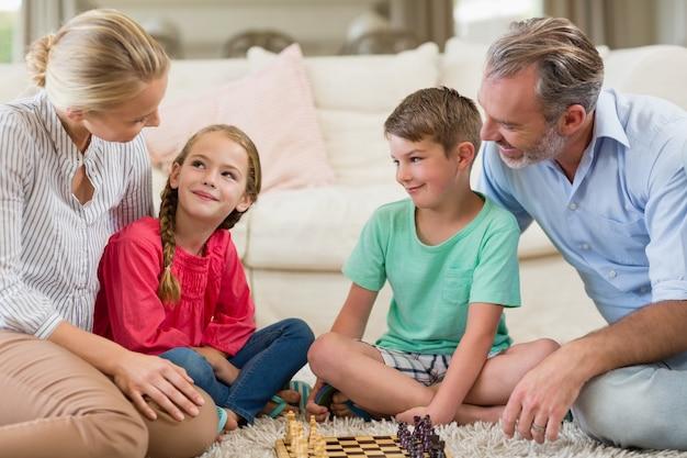 Famille jouant aux échecs ensemble à la maison dans le salon