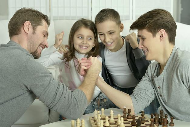 Famille jouant aux échecs sur une table à la maison