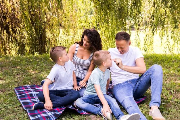 Famille jouant sur une couverture de pique-nique