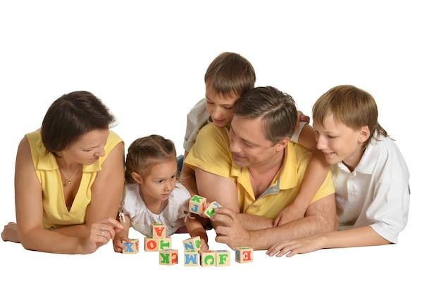 Famille jouant avec des cubes isolés sur blanc