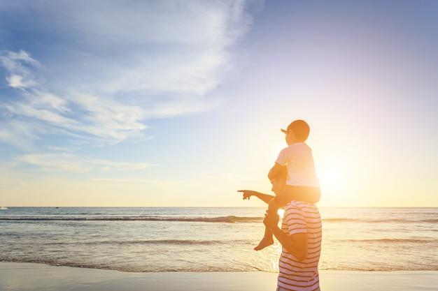 Famille jouant avec le fils sur la plage au coucher du soleil