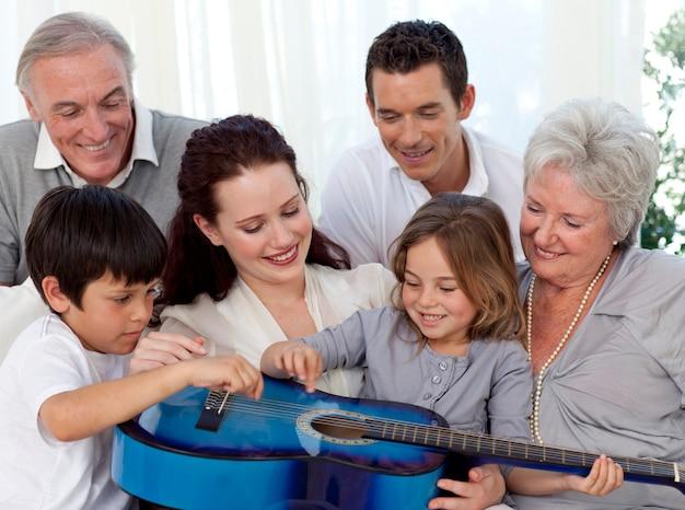 Famille jouant de la guitare dans le salon