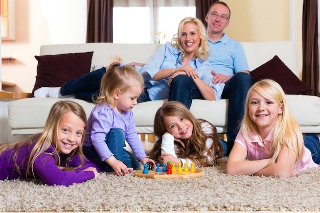 Famille jouant à un jeu de société à la maison