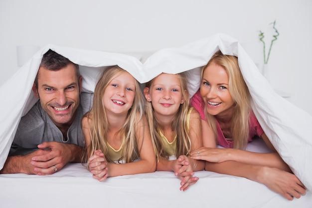 Famille jouant sous la couette au lit