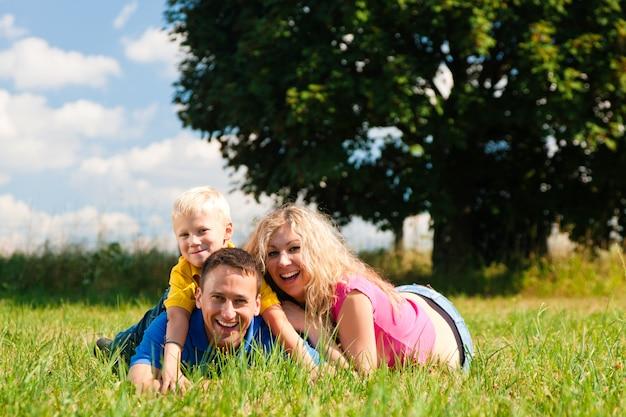 Famille jouant tag sur prairie en été
