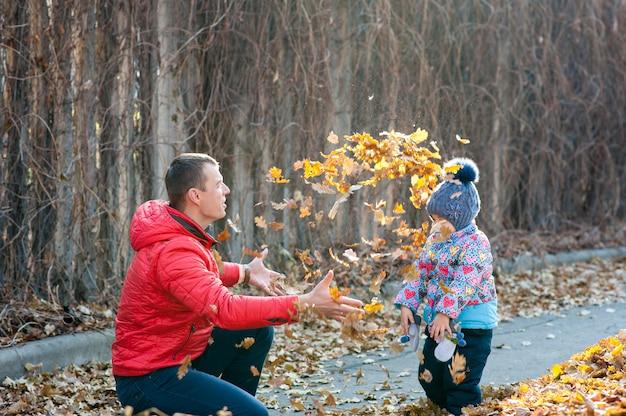 La famille a joué dans les feuilles du parc