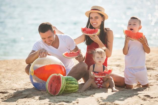 Famille joyeuse, manger de la pastèque sur la plage. les petits enfants et leurs parents au bord de la mer s'amusent. famille joyeuse au bord de la mer