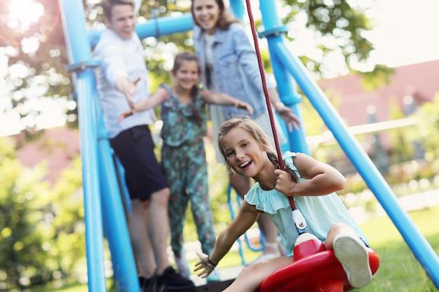 Famille joyeuse s'amusant sur l'aire de jeux
