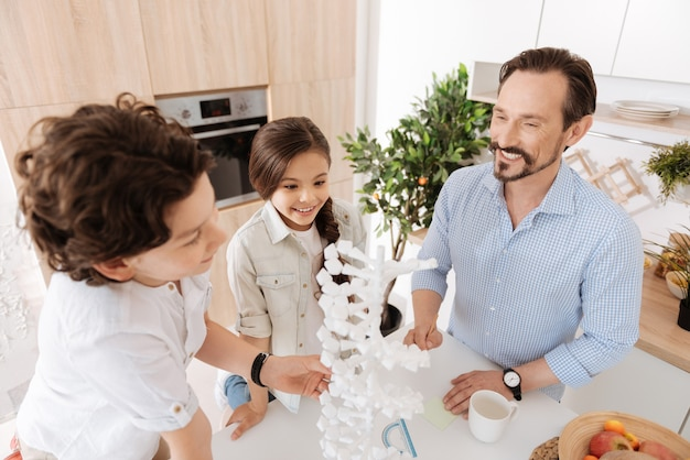 Famille joyeuse et soudée debout autour d'un grand modèle d'adn 3d, le scrutant tout en ayant l'air inspiré et heureux d'étudier ensemble