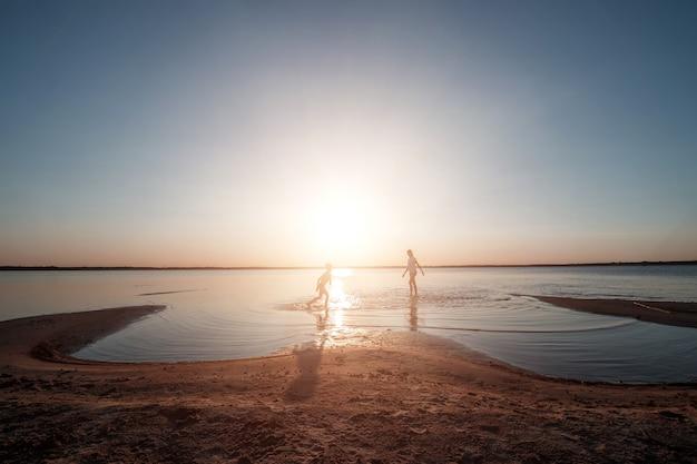 Famille sur le lac contre un beau coucher de soleil.