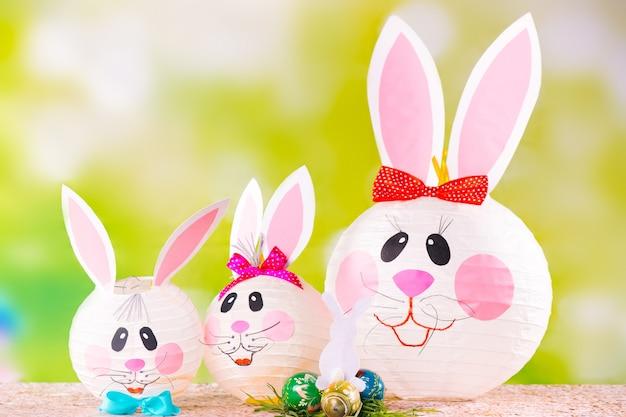Famille de lapins de pâques décoratifs faits à la main sur un vert