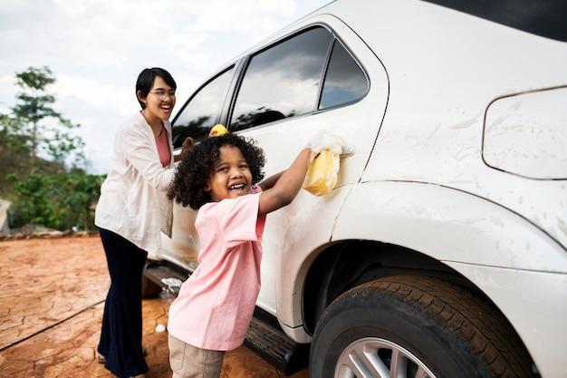 Famille lavant leur voiture blanche