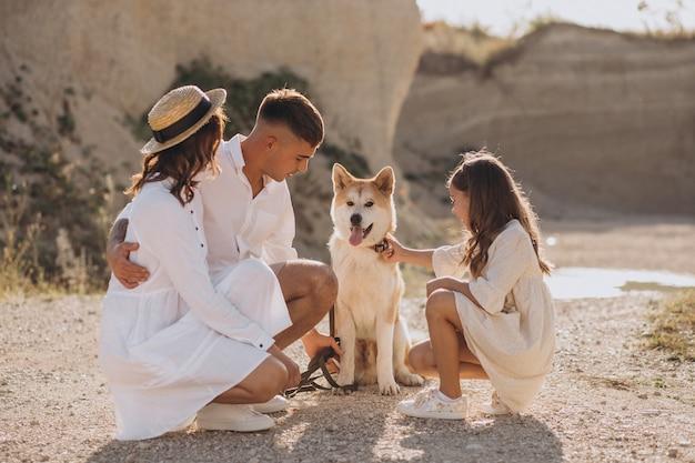 Famille avec leur fille et leur chien sortant