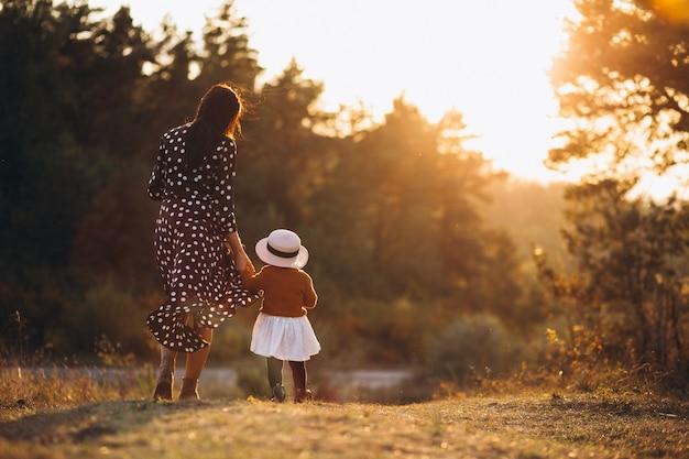 Famille avec leur petite fille dans un champ d'automne