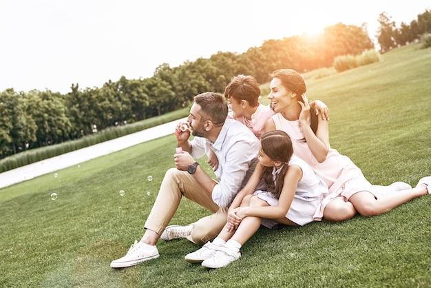 Famille de liaison de quatre personnes assises sur un champ herbeux soufflant des bulles