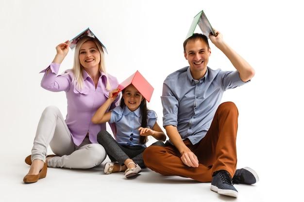 Famille lisant un livre ensemble allongé sur le sol à la maison