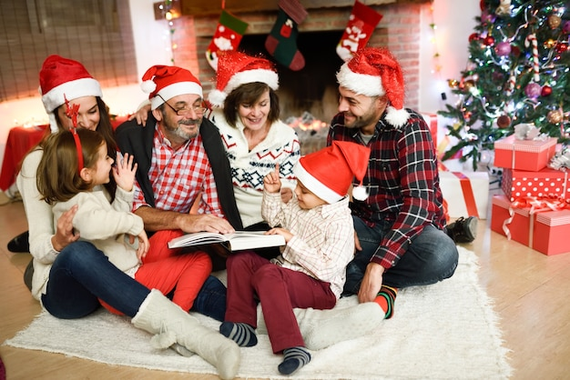 Famille lisant un livre ensemble dans leur salon