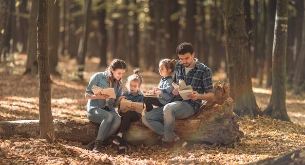 Famille lisant des livres dans la forêt.