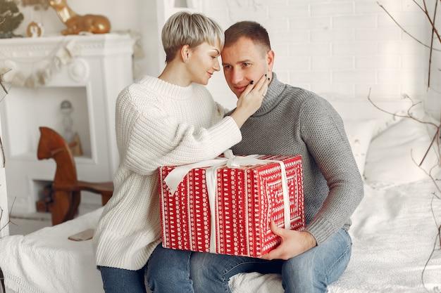 Famille à la maison. couple près de décorations de noël. femme dans un pull gris.