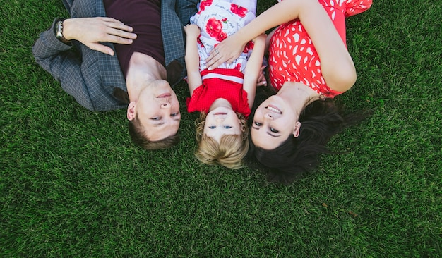 Famille, maman, papa et fille heureuse et belle couchée sur l'herbe verte avec des sourires