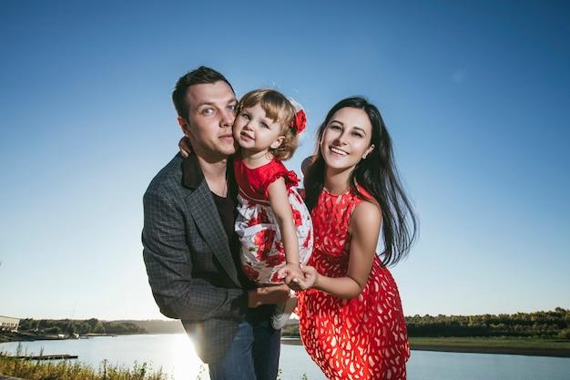 Famille, maman, papa tenant la fille heureuse et belle promenade au coucher du soleil sur la jetée