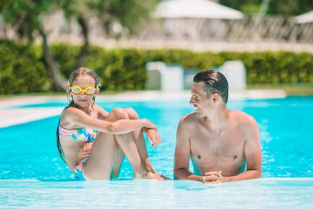 Famille de maman et petite fille profitant des vacances d'été dans une piscine de luxe