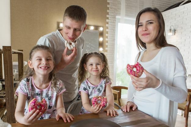 La famille mange des gâteaux le dîner à la fête de la boulangerie dans la cuisine le dépeçage de la nourriture