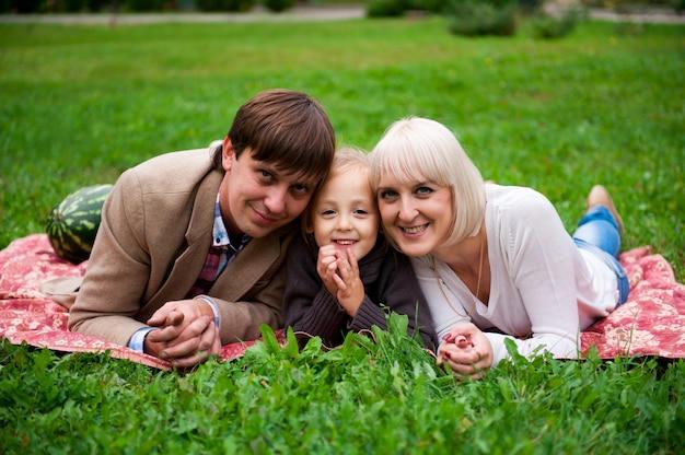 La famille mange une pastèque ensemble dans le parc.