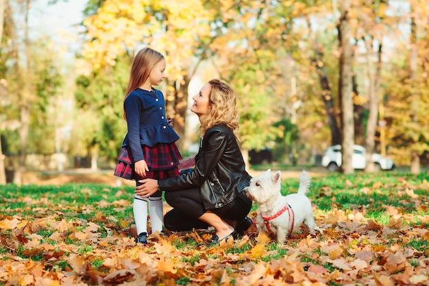 Famille marchant avec chien dans le parc de l'automne.