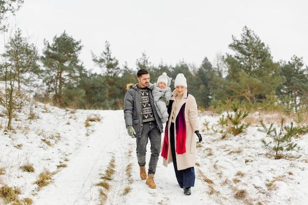 Famille marchant dans la neige s'amusant dans le parc d'hiver par un beau jour se serrant les uns les autres et souriant