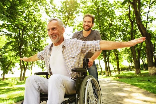 Famille marchant dans le parc handicapé en fauteuil roulant