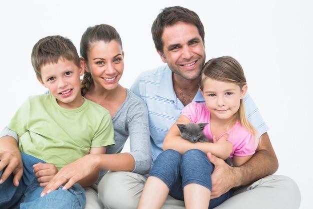 Famille mignonne avec chaton pour animaux de compagnie posant et souriant à la caméra ensemble
