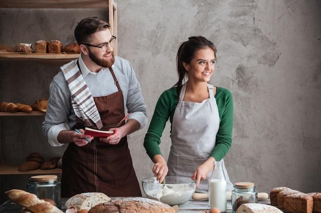 Famille mignonne en détournant les yeux pendant la cuisson du pain