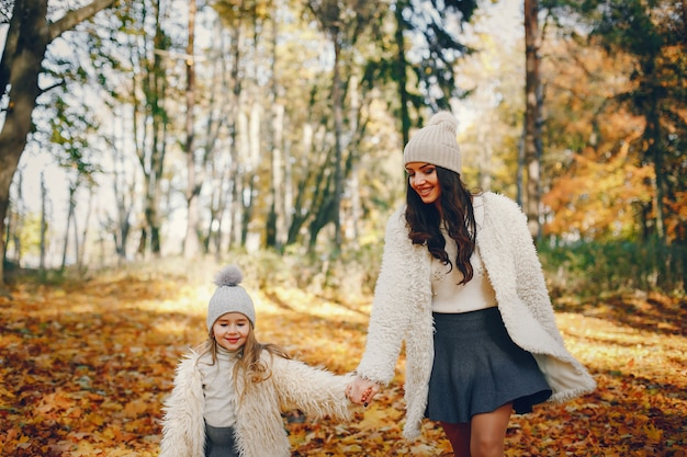 Famille mignonne et élégante dans un parc en automne