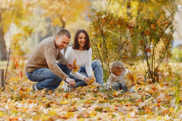 Famille mignonne et élégante jouant dans un champ d'automne
