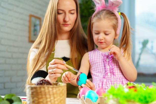 Famille mignonne, mère et fille se préparant pour la célébration de pâques