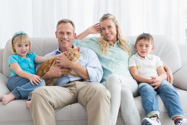 Famille mignonne se détendre ensemble sur le canapé avec leur chat
