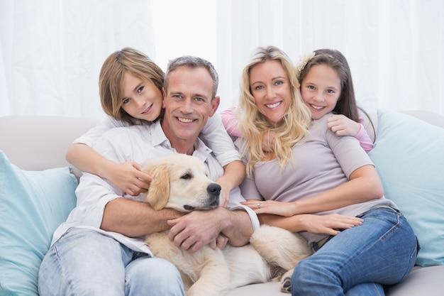 Famille mignonne se détendre ensemble sur le canapé avec leur chien