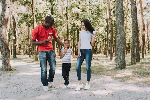 Famille mixte heureuse manger de la crème glacée dans la forêt.