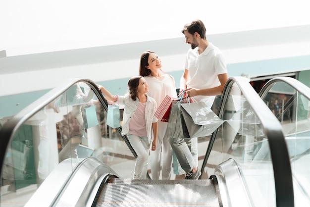 La famille monte sur l'escalator dans un centre commercial.