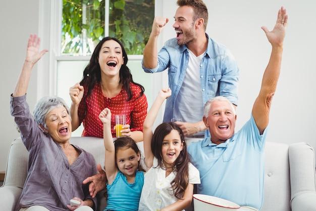 Famille multi génération acclamant sur le canapé
