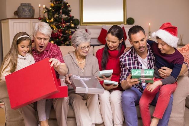 Famille multi génération ouvrant des cadeaux sur le canapé
