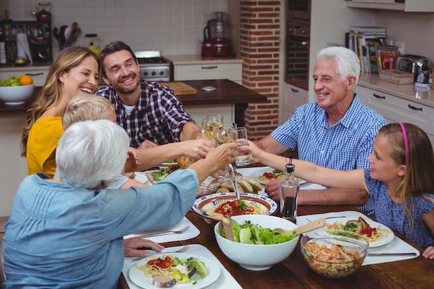 Famille multi génération portant un toast au vin blanc tout en célébrant l'action de grâce