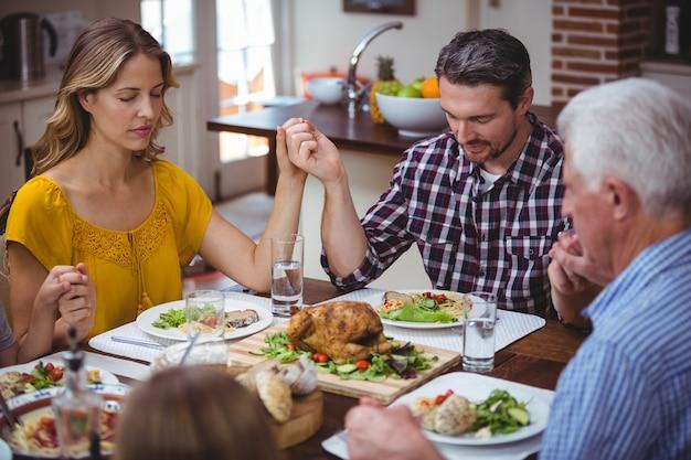 Famille multi-génération se tenant la main en priant