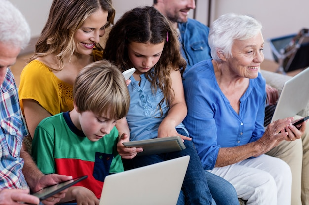 Famille multi-génération utilisant un ordinateur portable, une tablette et un téléphone
