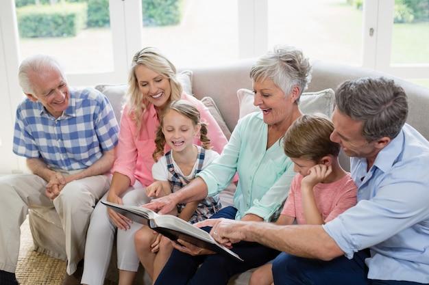 Famille multi-générationnelle regardant sa photo d'album dans le salon