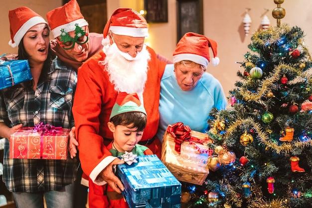 Famille multi-générationnelle s'amusant la nuit de noël en se donnant des cadeaux x mas