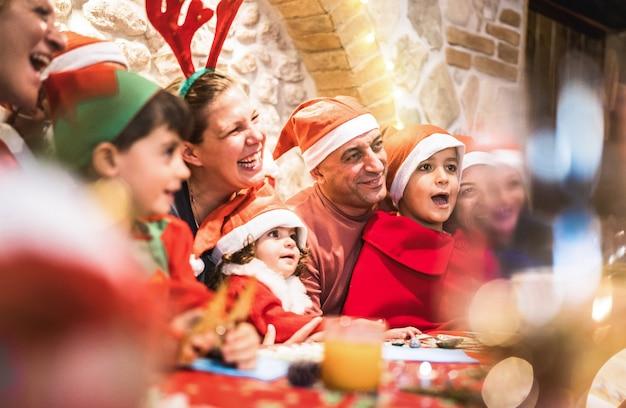 Famille multi-générationnelle sur des vêtements de bonnet de noel s'amusant à la fête de la fête de noël