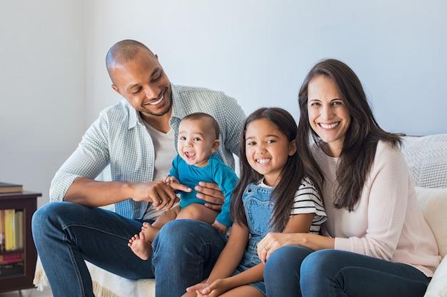 Famille multiethnique heureuse sur canapé
